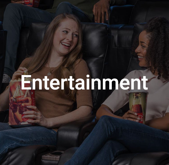 Dark overlay with text saying entertainment over image of girls enjoying their time at the movies.