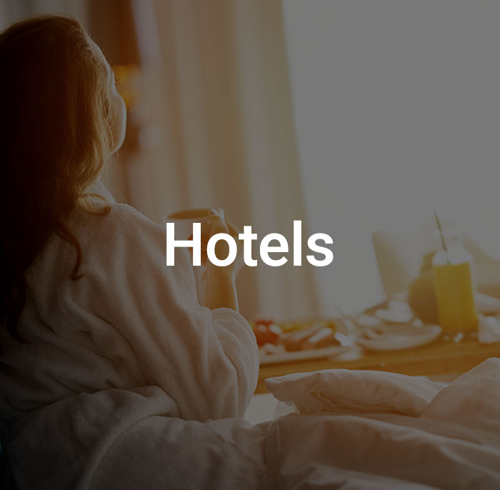 Dark overlay with text that reads hotel over image of woman enjoying breakfast in bed in front of a window.