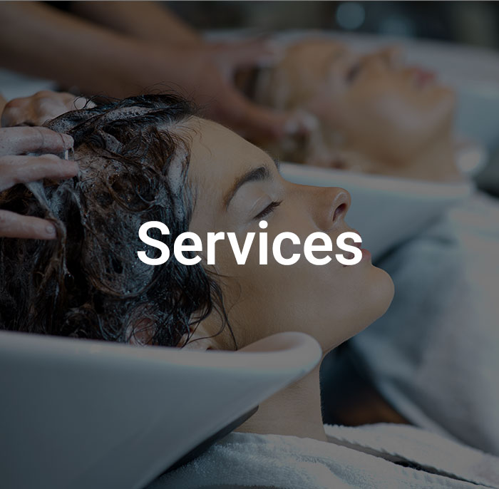 Dark overlay with text that reads services on image of women getting their hair shampooed at a salon.