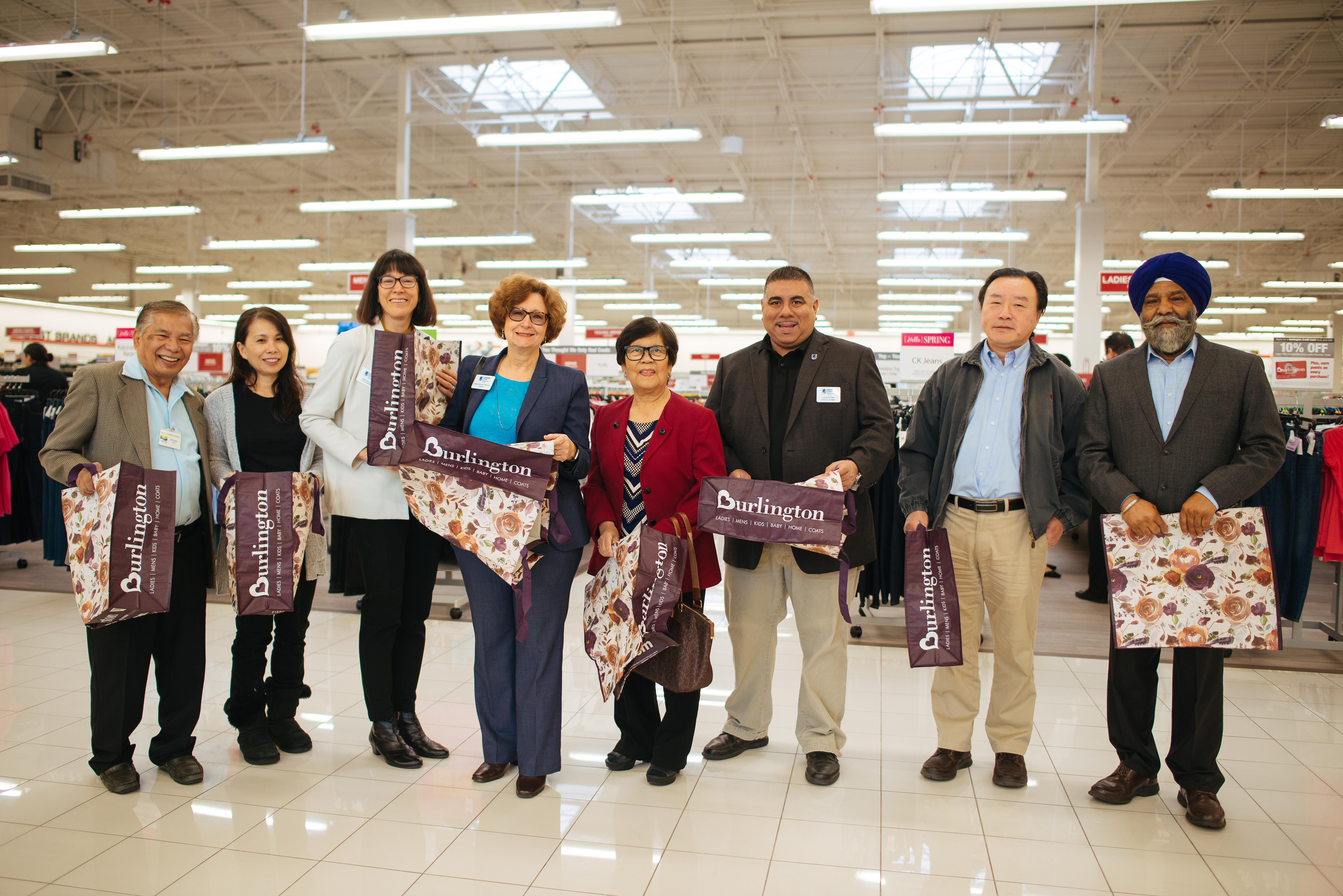 Representatives inside Burlington holding floral Burlington tote bags.