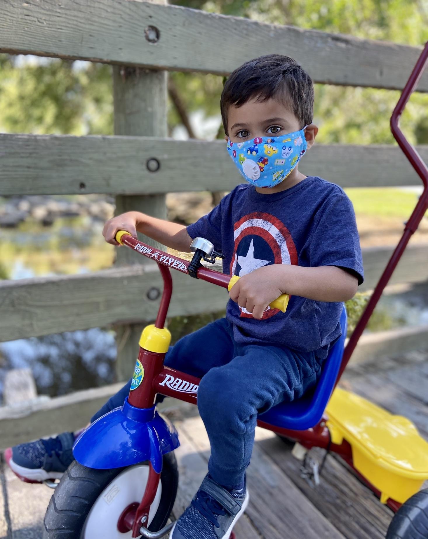 kid wearing a mask on a bike