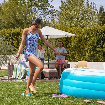 Kids playing outside for summer near an inflatable pool.